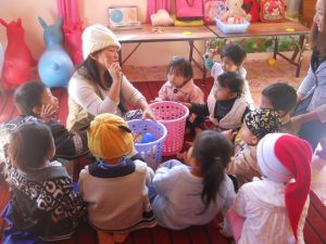 Teacher and kids play a game at the Pwin Oo Lwin preschool.