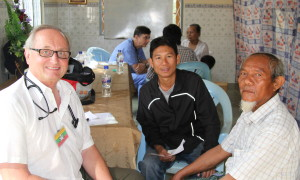 Dr. Dwain Illman of Bloomington, IN meets a patient during a FAME mission trip to Myanmar in January 2014.  Assisting him as translator is Josiah Aung, director of Hope.