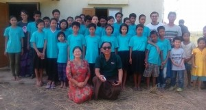In their blue shirts, children happily pose with visitors.  In the front row in Maeram, educational coordinator for ACM.  Sweet, in the sunglasses, came along to play the keyboard for the Thanksgiving celebration.